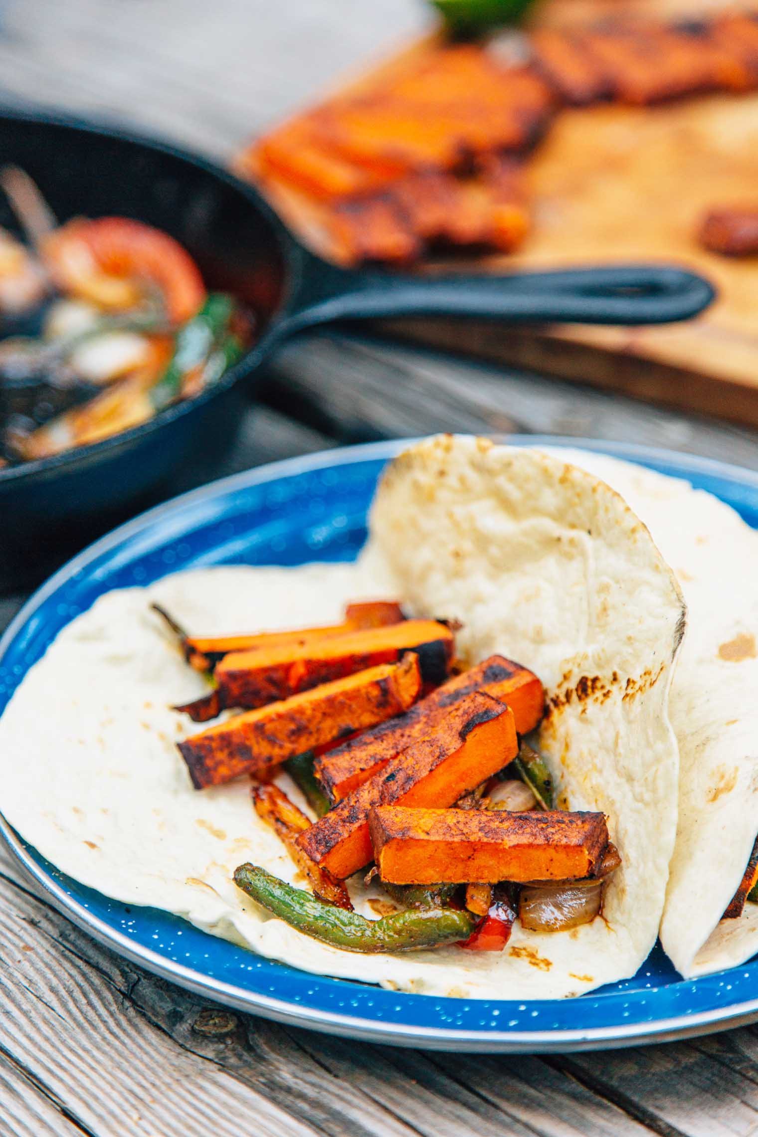 """Grilled sweet potato """"steaks"""", roasted peppers and onions, and a New Mexican chile marinade, these vegan campfire fajitas are a new take on an old classic"""