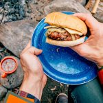 Apple cheddar burger on a blue camping plate in front of a campfire.