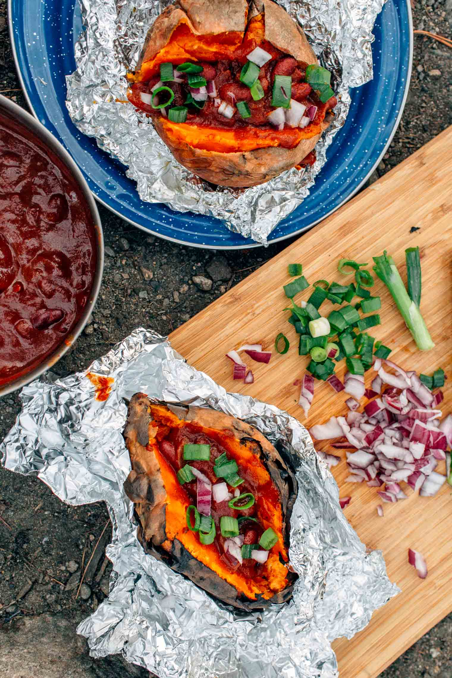 Foil wrapped sweet potatoes and chili on a blue camping plate.