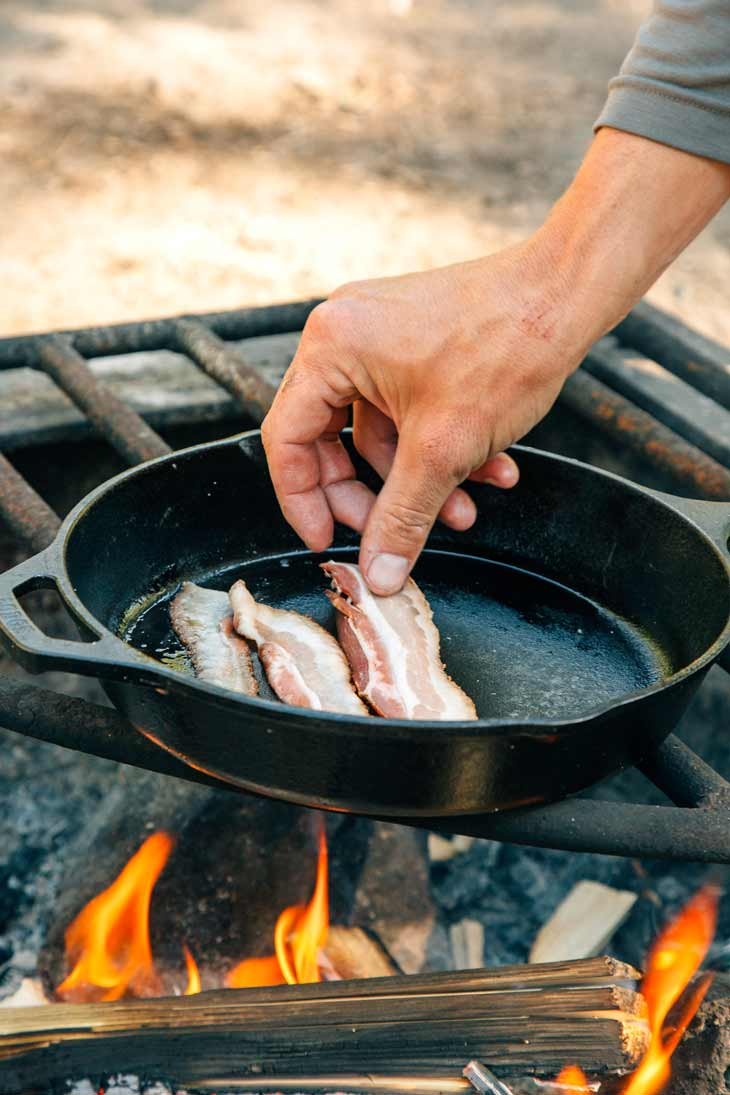 Cooking bacon in a skillet over the campfire