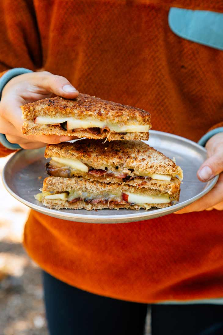 Holding an Apple Bacon Cheddar Grilled Cheese sandwich