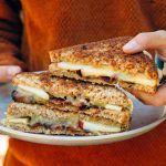 Holding a Apple Bacon Cheddar Grilled Cheese Sandwich