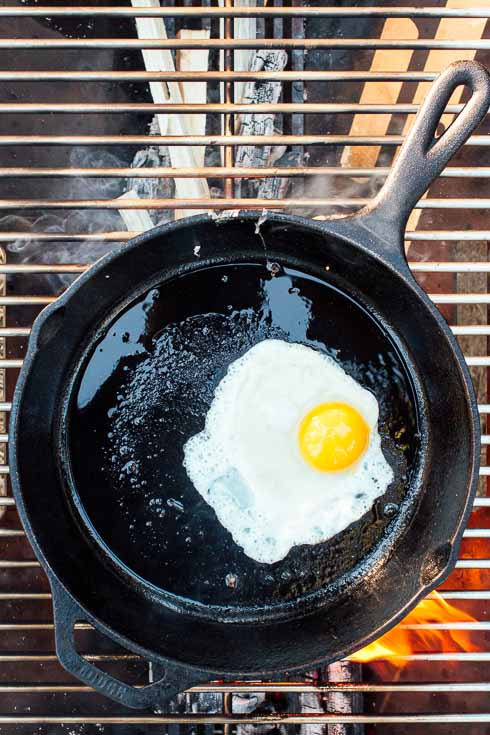 Sunny side egg in a cast iron skillet over a campfire