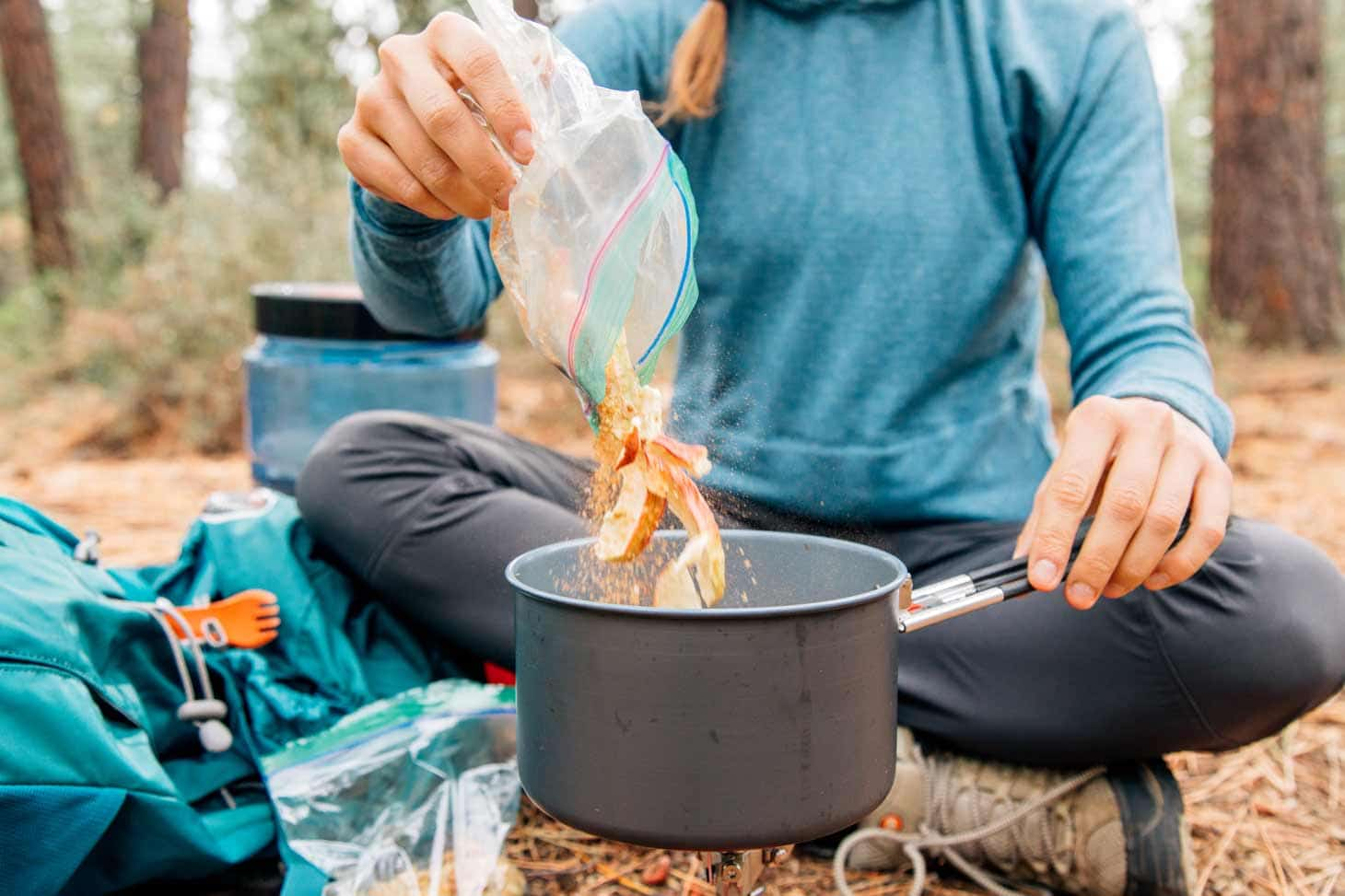 Woman pouring apples into a backpacking pot