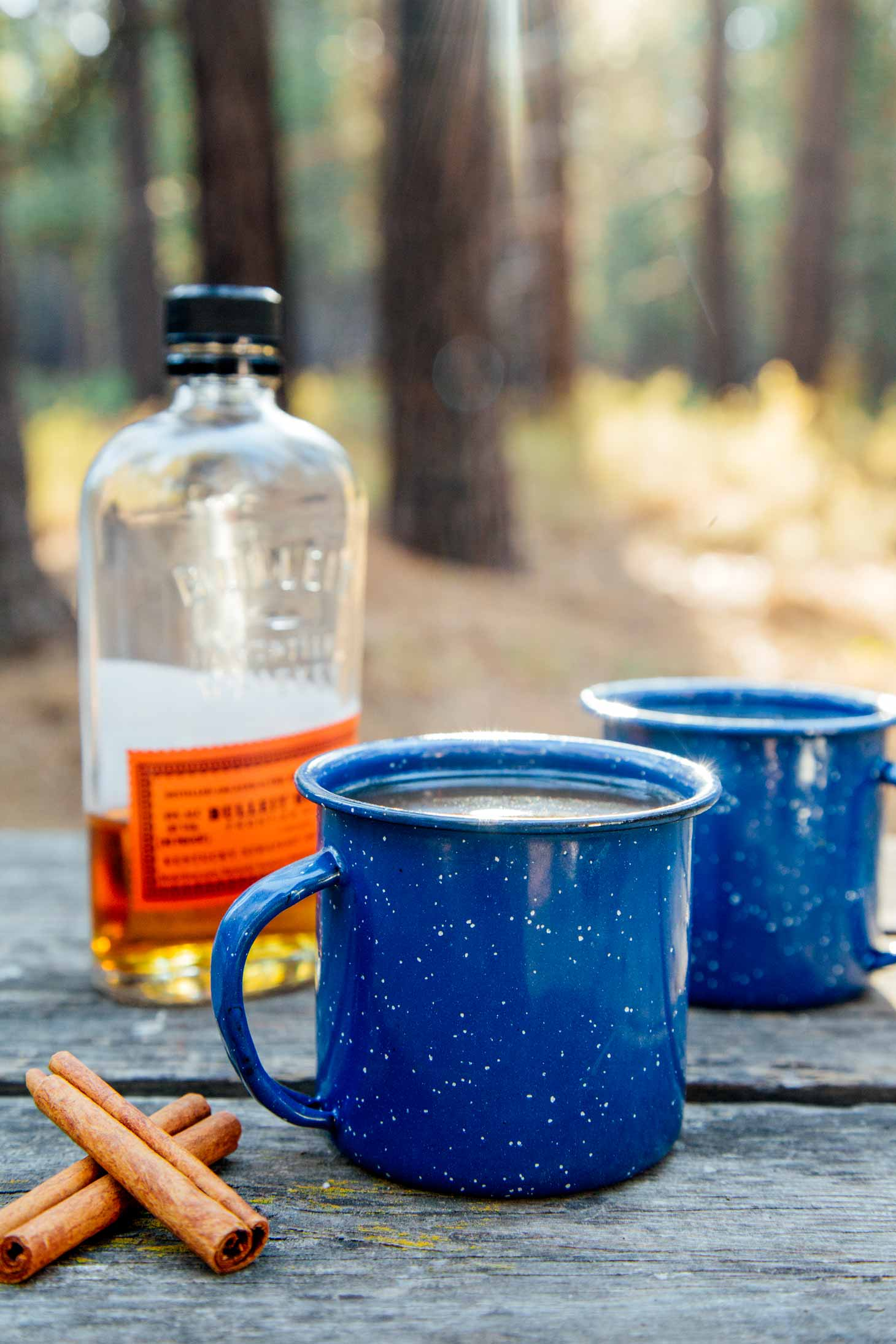 Forest scene with two camping mugs of spiked apple cider with a bottle of bourbon in the background.