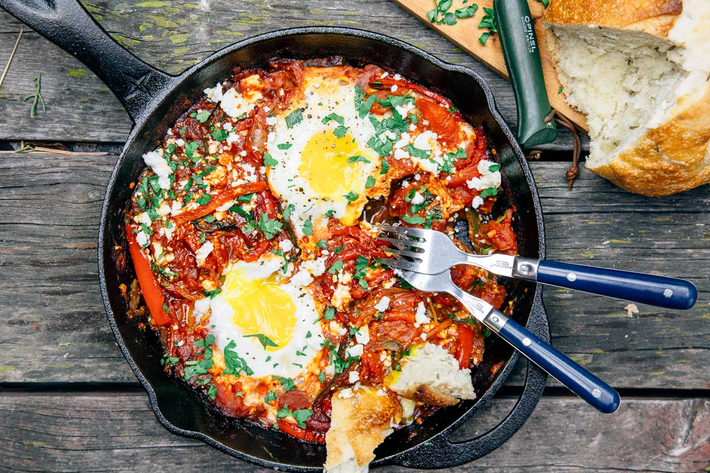 Shakshuka in a cast iron skillet with two eggs and bread