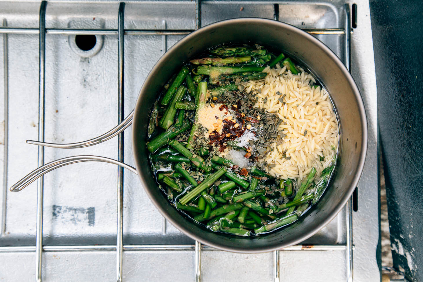 Ingredients for asparagus orzo in a cooking pot on a camping stove