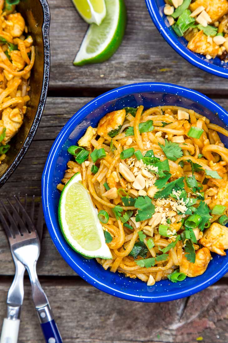 Pad thai in a blue camping bowl on a wooden surface