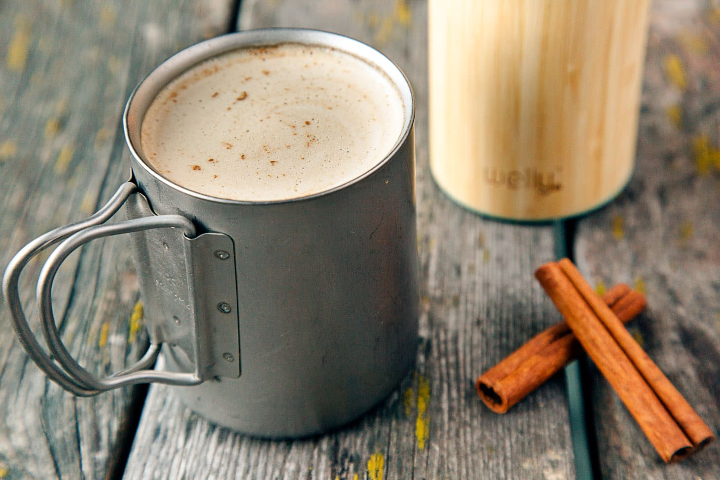 Cinnamon Coconut Latte in a camping mug on a wooden table.