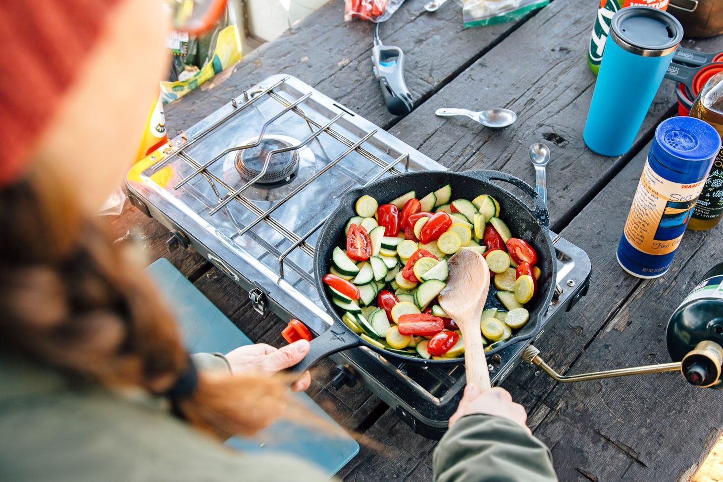 Sauteeing tomatoes, zucchini, and yellow summer squash in a cast iron skillet on a camping stove.