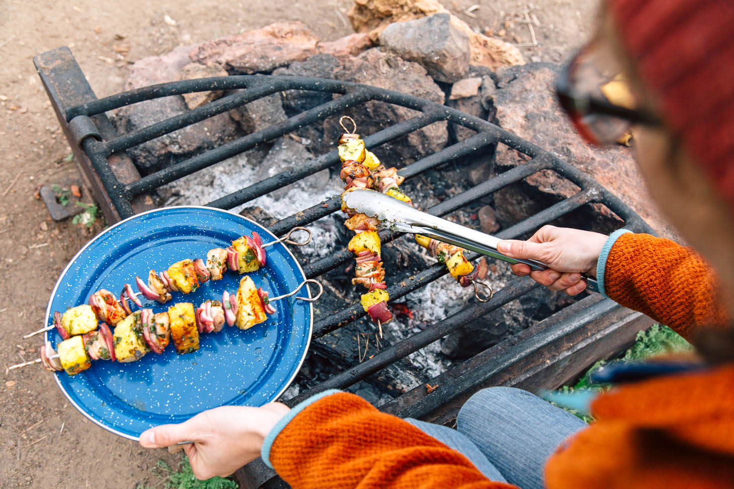 Grilling chicken pineapple kabobs over a campfire