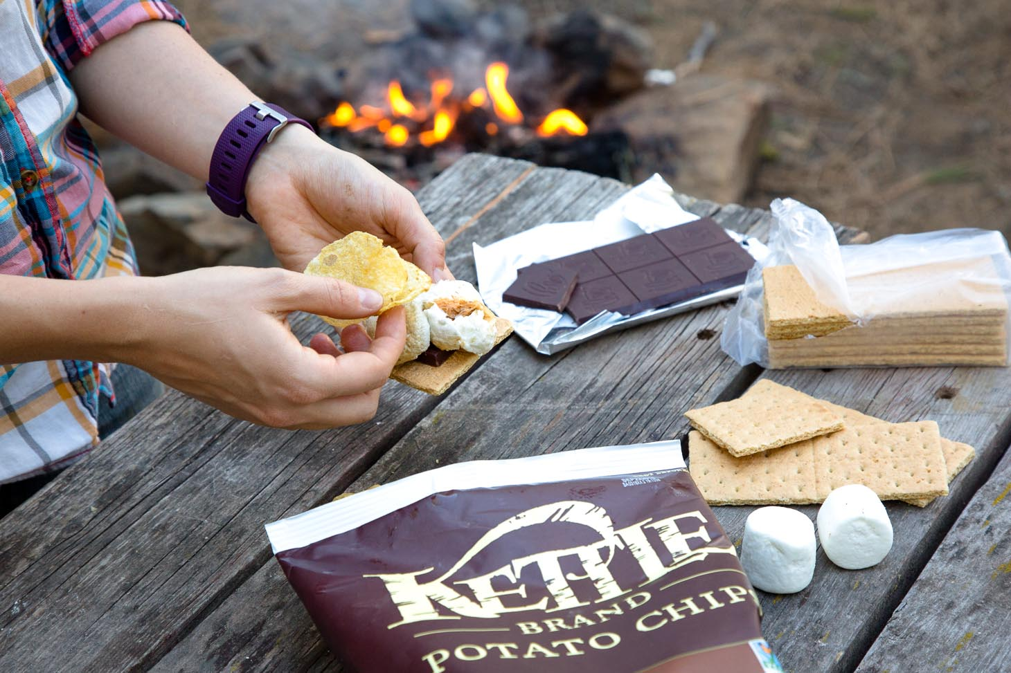 S'more ingredients (chocolate, marshmallows, and graham crackers) on a picnic table.