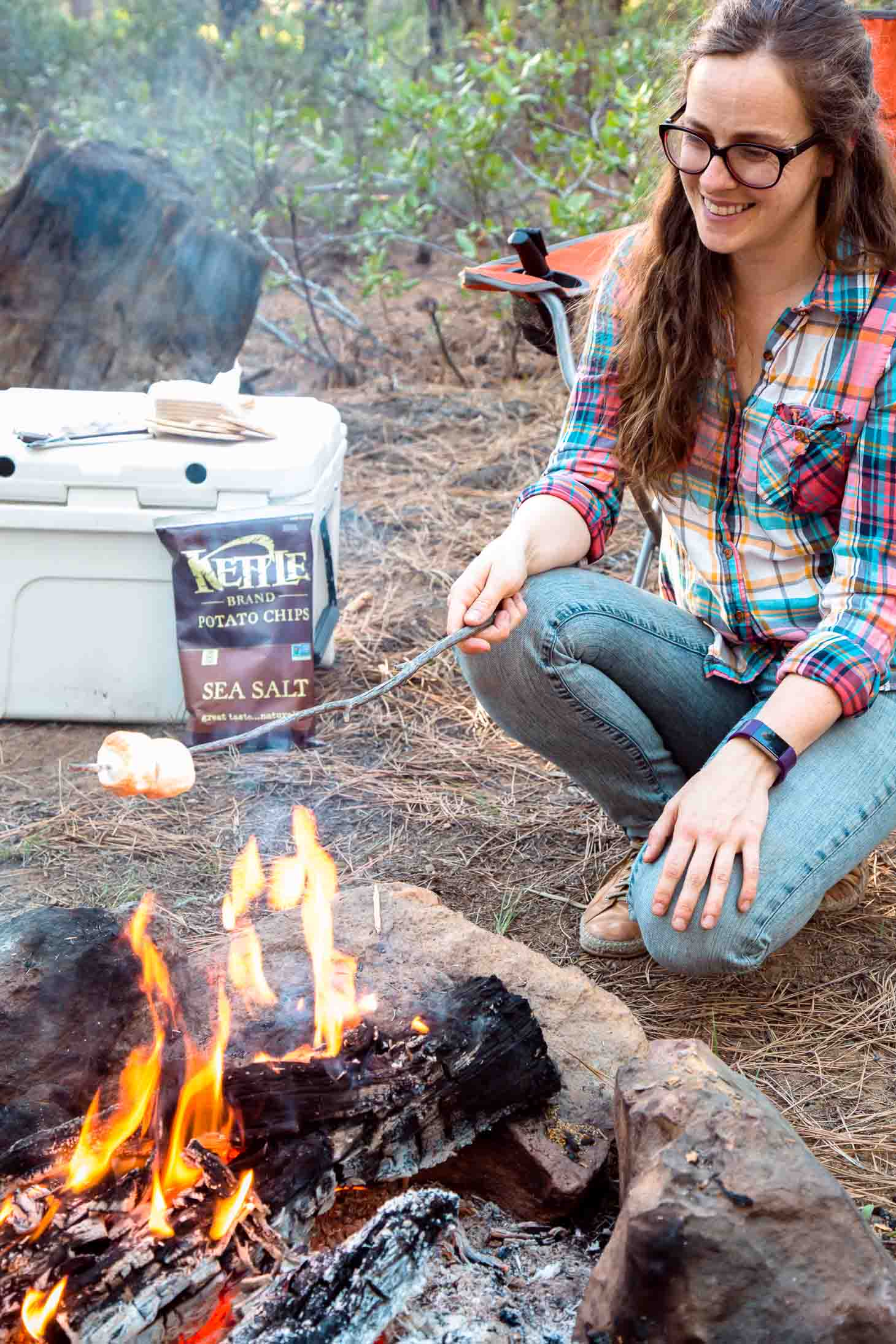 Woman roasting marshmallows over a campfire.