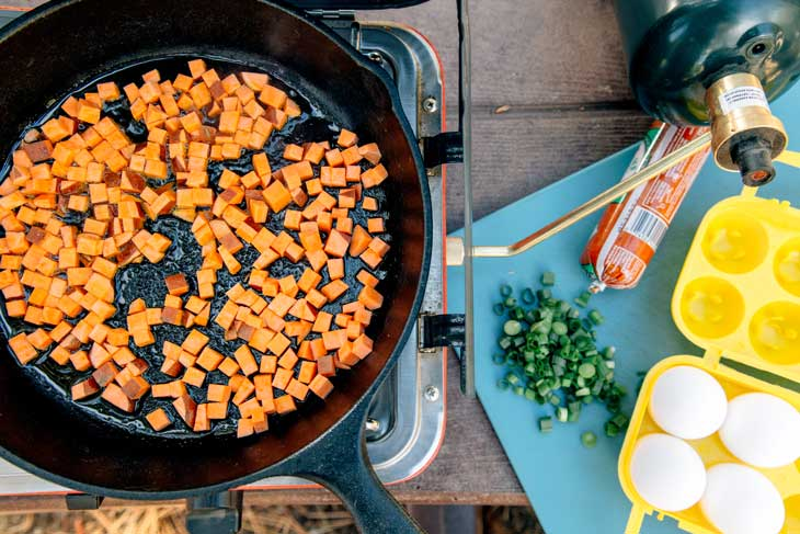 Diced sweet potato in a cast iron skillet for breakfast hash.