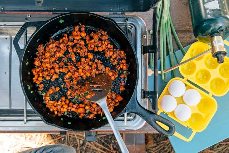 Cooked chorizo and sweet potatoes in a camping skillet