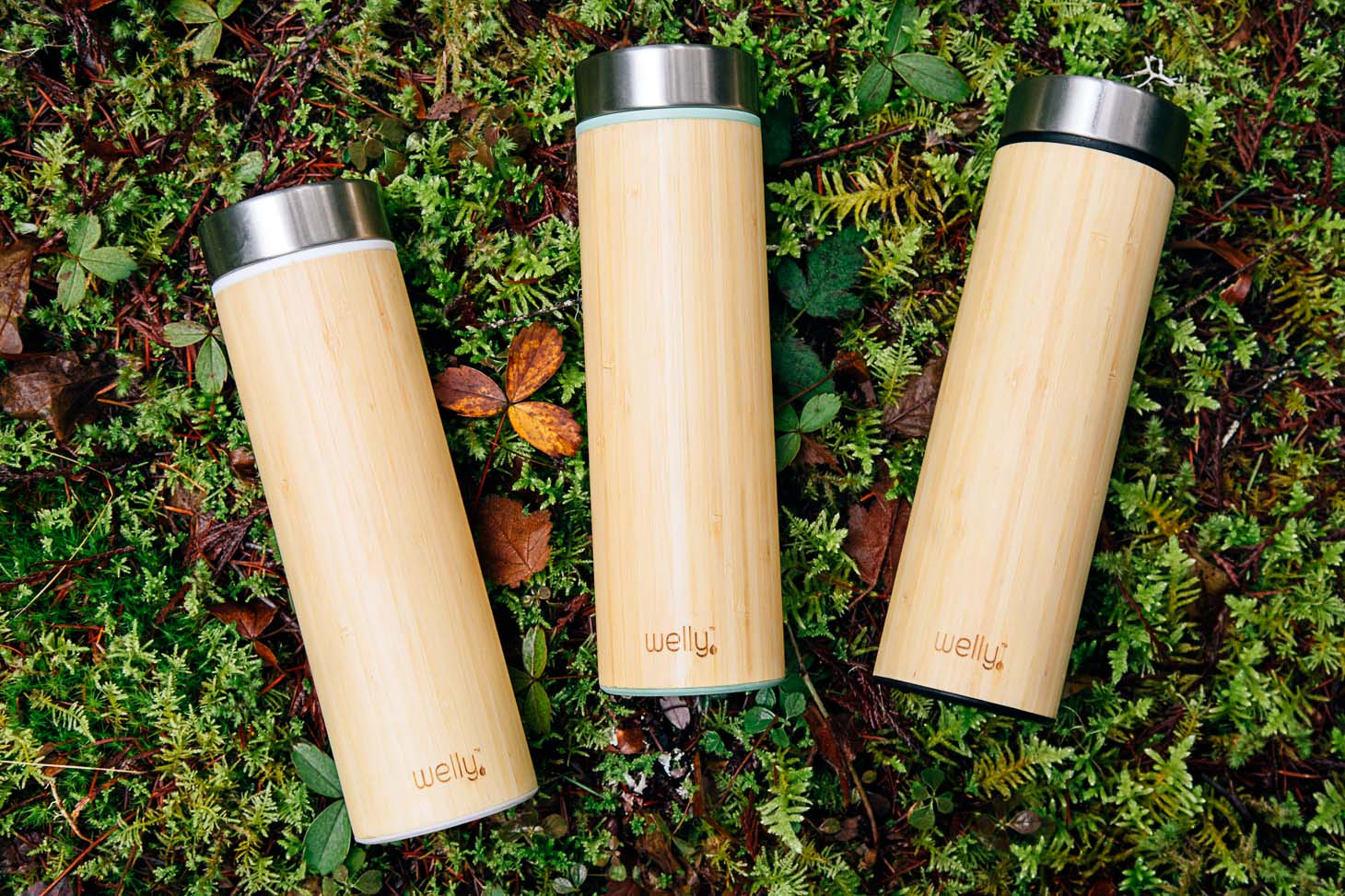 Three bamboo water bottles on a mossy surface.